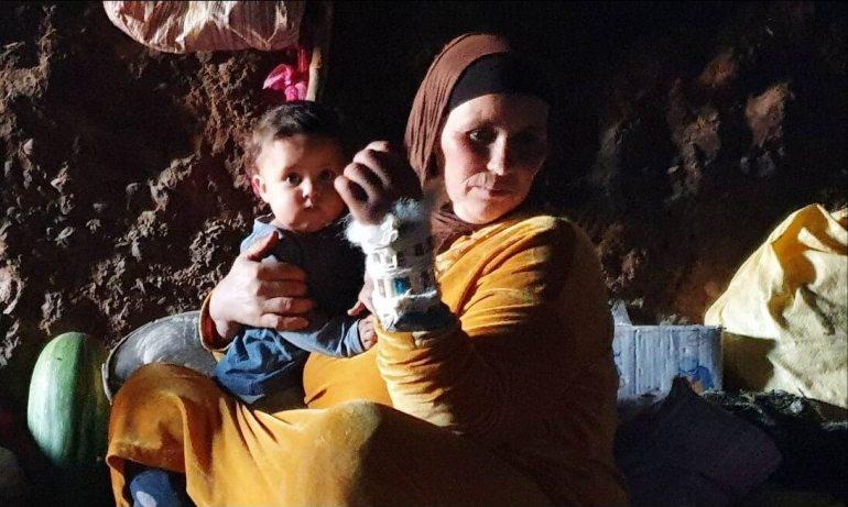 femme berbère portant un bébé et vivant dans une grotte au maroc