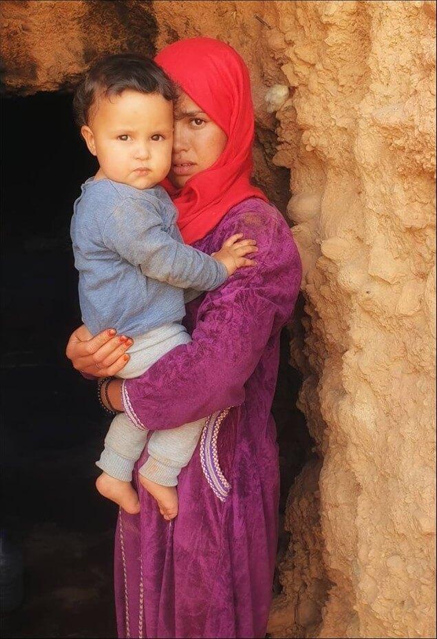 fillette tenant un enfant dans ses bras à l'entrée d'une grotte dans l'atlas marocain