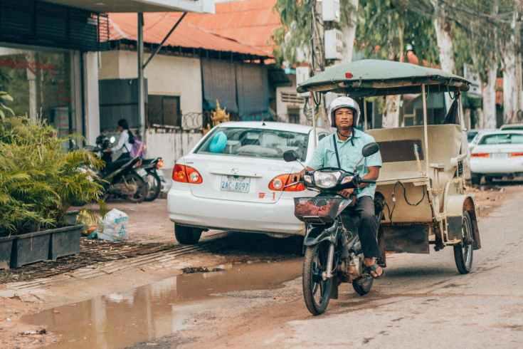man riding motorcycle near white car