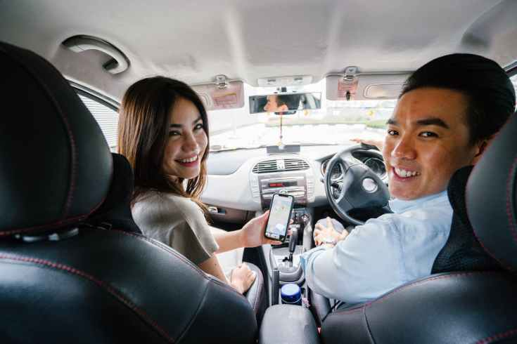 smiling man and woman sitting inside vehicle