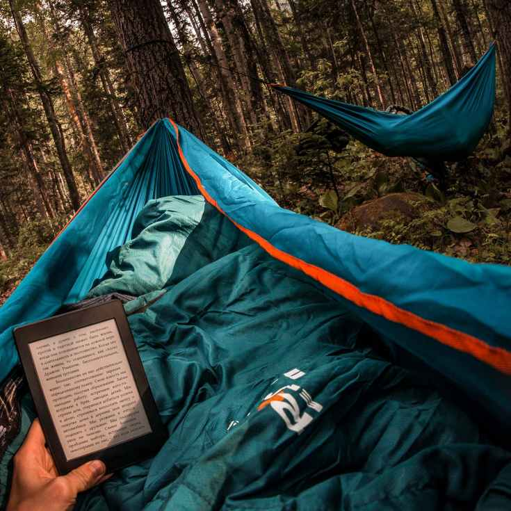 person holding amazon kindle while laying on hammock