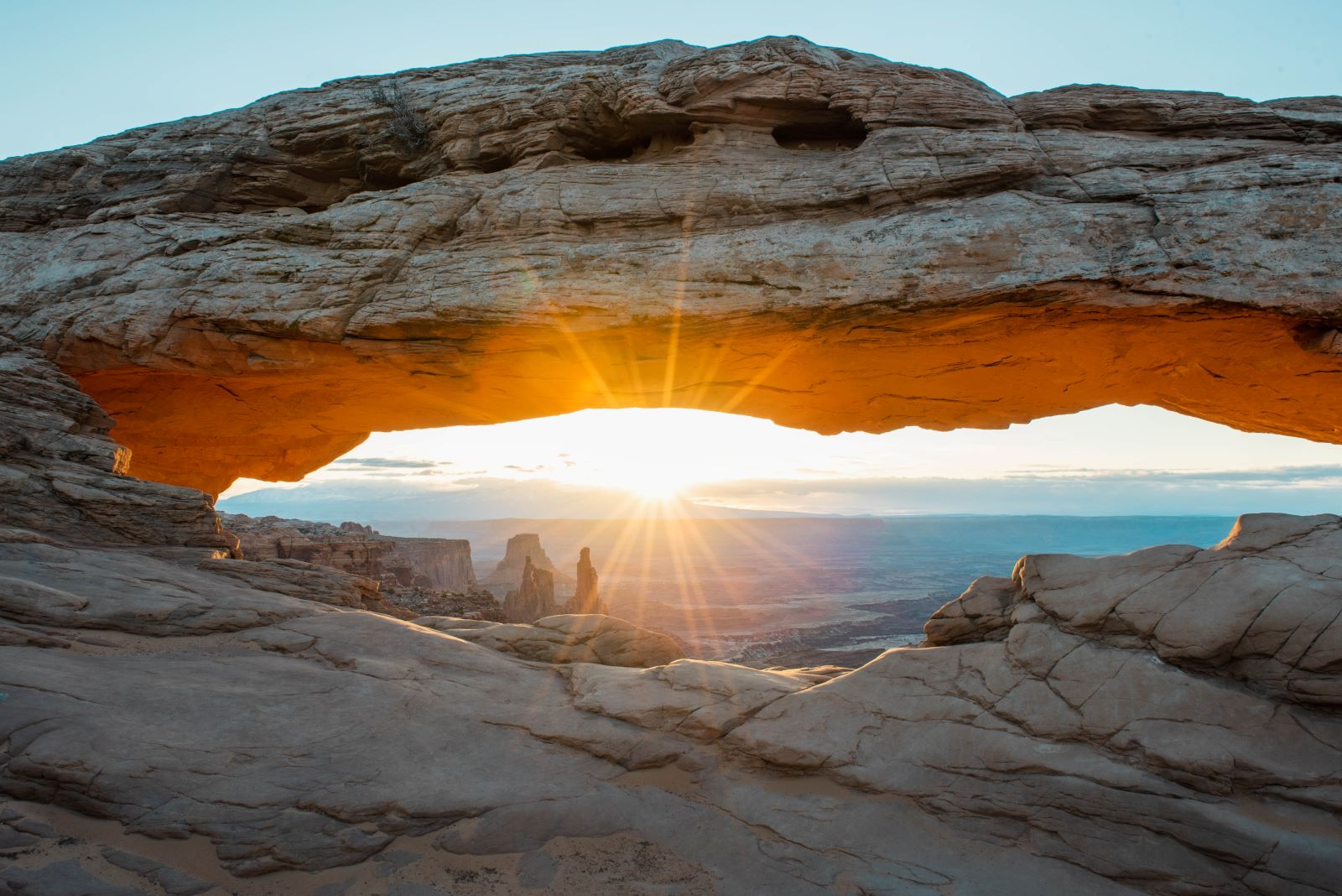Mesa arch at sunrise glowing red with sun starburst