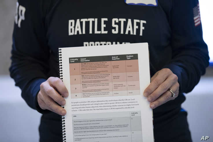 In this Monday, Dec. 16, 2019, photo, a booklet is held up during an exercise run by military and national security officials,…