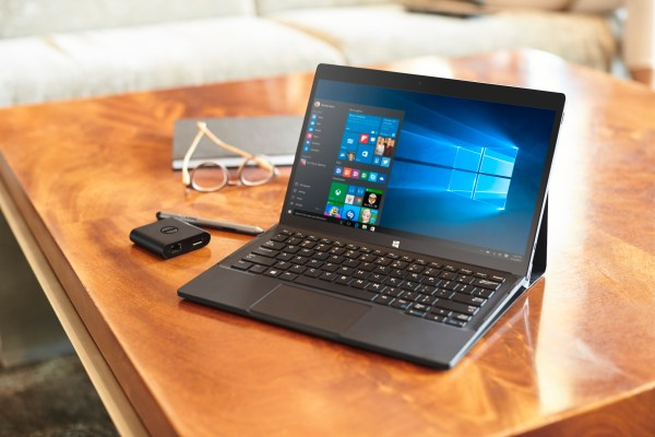 Dell XPS 12 (Model 9250) 2-in-1 notebook computer with Premier Folio, Dell USB Adapter Type-C HDMI/VGA/Ethernet/USB 3.0 (Slayer), and Active Stylus (Juniper) on a wooden coffee table in a bright lobby with a pair of glasses and notebook beside it. A tan c