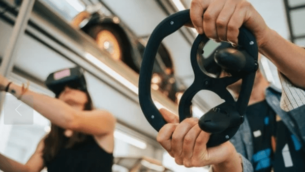 A man and a woman holding 3D printed custom-designed steering wheels that house Oculus Quest controllers