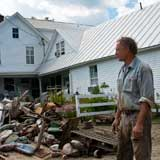 George Schenk, owner of American Flatbread and the Inn at Lareau Farm in Waitsfield, looks over a pile of flood ravaged goods removed from the inn and restaurant. VTD/Josh Larkin