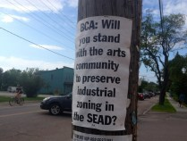 """A sign reading, """"BCA: Will you stand with the arts community to preserve industrial zoning in the SEAD?"""" on Pine Street in the South End, challenges how the city agency tasked with outreach on a development proposal - Burlington City Arts - should be supporting artists. Photo by Jess Wisloski/VTDigger"""