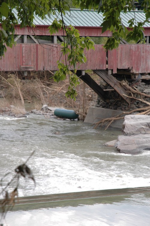 The broad span of the iconic Taftsville Covered Bridge on Rt. 4 is closed after Sunday's flood due to foundatin concerns and a large propane tanks sits in the Ottauquechee River below. VTD/Andrew Nemethy