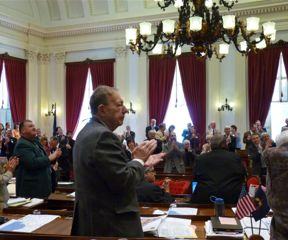 Rep. Tom Koch, R-Barre, foreground and other lawmakers clap on the House floor. Photo by Ceilidh Galloway-Kane
