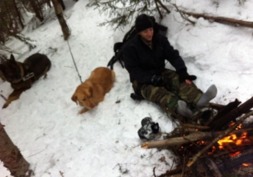 Photo 2 is identified in the public records release as having been taken by VSP Sgt. Robert Patten on January 10, 2012. It shows an unidentified member of the search team warming his feet at the fire which records indicate was built to warm Levi Duclos' dog (the yellow dog in the picture) who survived the night with him. The photo shows the searcher's snow-encrusted light (not winter) hiking boots, cotton camo pants, and what look like wet gray cotton socks. VSP photo