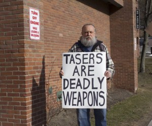 Morgan Brown protests a Taser hearing outside a Montpelier public forum on March 11, 2013. Photo by Nat Rudarakanchana
