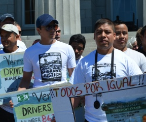 "Migrant workers hold up signs depicting Vermont driver's licenses at a bill-signing Wednesday in Montpelier that allows them to obtain ""operator's privilege cards"" so they can drive in the state with or without documentation. Photo by Alicia Freese/VTDigger"