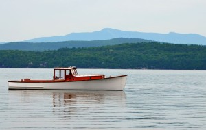 "The Maddy Sue, a beautifully restored 1932 ""lobster yacht"" from Maine, floats on Lake Champlain with Mt. Mansfield in the distance. Jan Rozendaal's passion for wooden boats led to him to buy and restore the iconic craft, one of several he now owns. Photo by Andrew Nemethy"