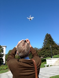 Allen Gilbert, executive director of the ACLU-VT, takes a photo of a drone that flew over the Statehouse as part of the organization's presentation of a report on surveillance programs in the state on Tuesday. Photo by John Herrick/VTDigger