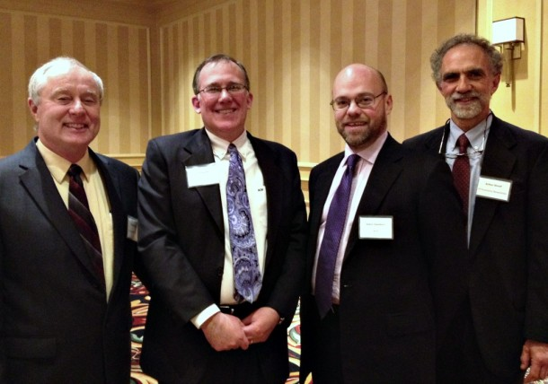 Dick Heaps, Gus Faucher, NPR's Adam Davidson and Art Woolf stand together after their presentations at the Vermont Economy Newsletter's 23rd annual conference, held in Burlington. Photo by Hilary Niles/VTDigger