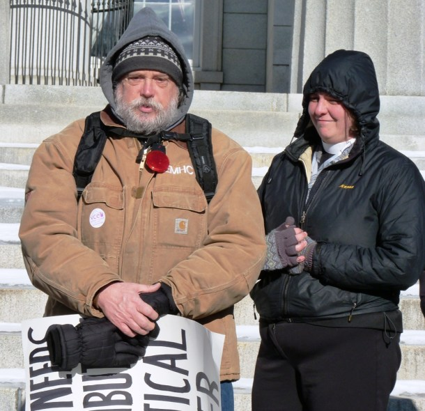 """What needs redistribution is political power,"" read the sign carried by Morgan Brown at a Homelessness Awareness Day event Thursday on the steps of the Statehouse in Montpelier. Photo by Anne Galloway/VTDigger"