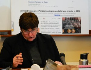 State Treasurer Beth Pearce references an enlarged screen shot of a news website, behind her. An ad for pension loans appears above an article quoting her concern about pension funding. Photo by Hilary Niles/VTDigger
