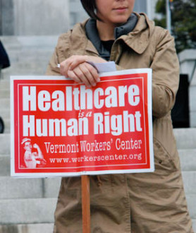 Demonstrator carries a sign from the Vermont Workers Center. Photo by John Herrick/VTDigger