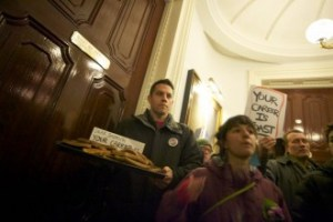 """James Haslam, executive director of the Vermont Workers Center, leaves a platter of toast outside the governor's ceremonial office at the Statehouse on Thursday, A sign directed at Gov. Peter Shumlin reads """"Your Career Is Toast.  Photo by John Herrick/VTDigger"""