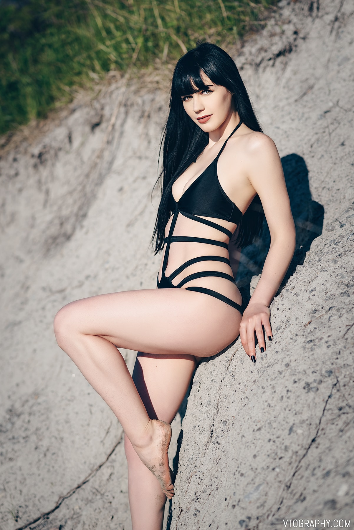 Ashley models a strappy black one-piece swimsuit from Zaful
