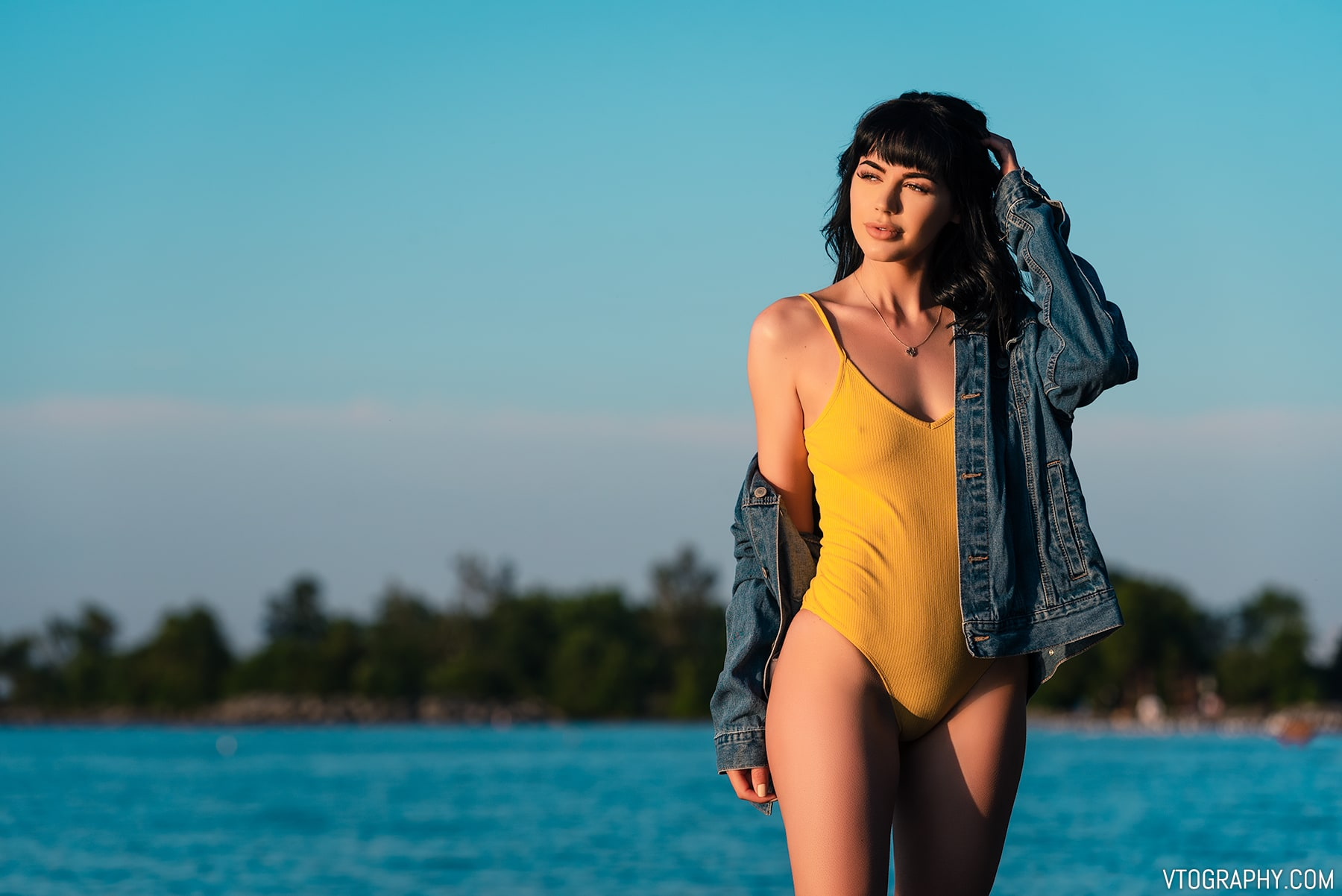 Model in yellow bodysuit and denim jacket
