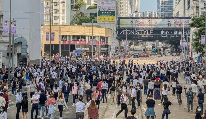 A crowd of people gathered in the street in Hong Kong.