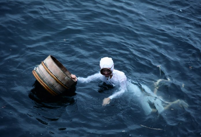 Japans traditional ama-san diver holding a barrel in blue water with white clothing and diving mask no oxygen tank and small tool around waist.