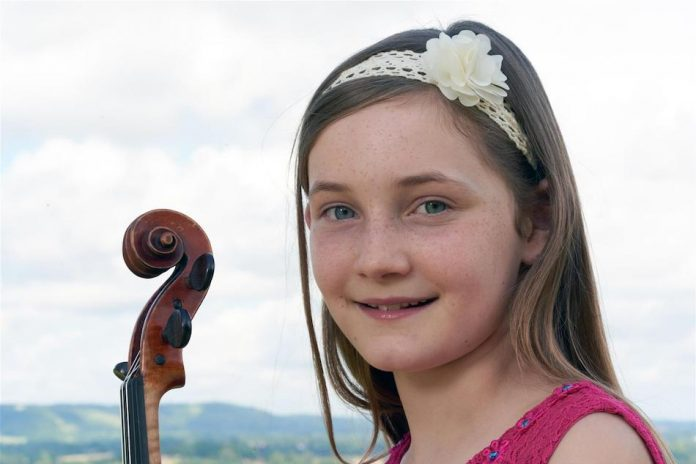 PortraiPortrait of musical child progidy alma deutscher with violin and white bow in her hair smiling and wears pink top