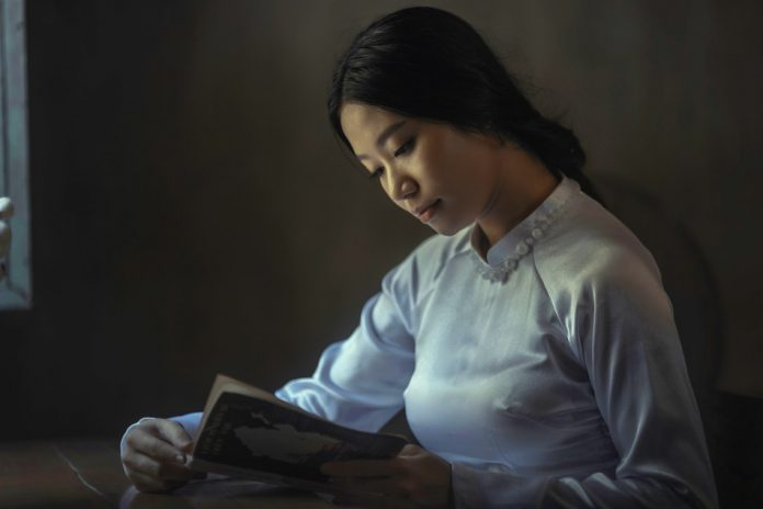 chinese lady with gentle face and traditional clothing reads a book