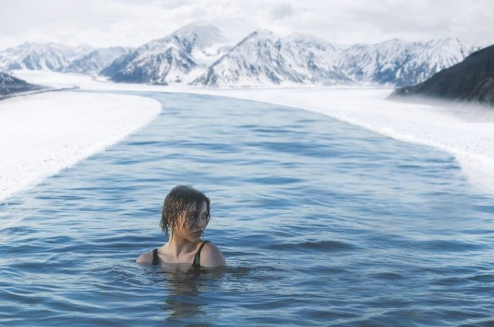 A young woman swims in a snowy mountain stream.