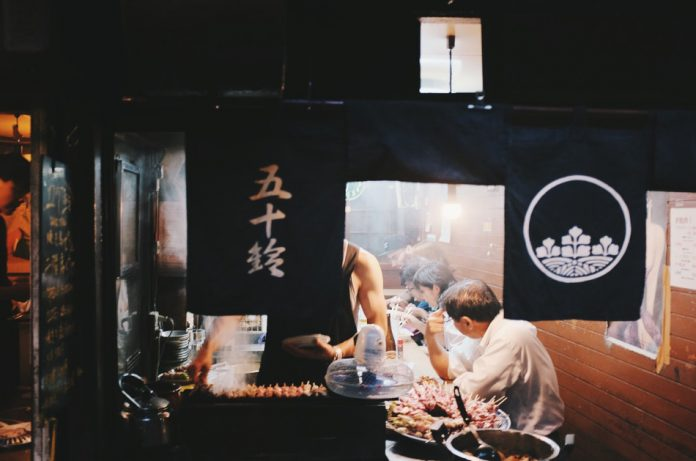 People eating at a counter in a Japanese restaurant while the chef grills meat in front of them.