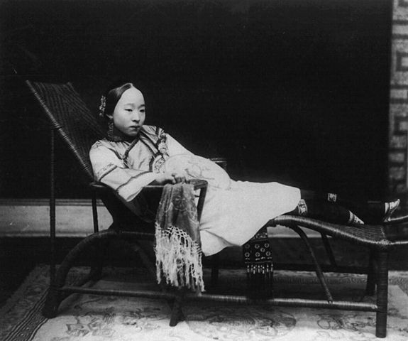 chinese girl with bound feet sit lays on chair