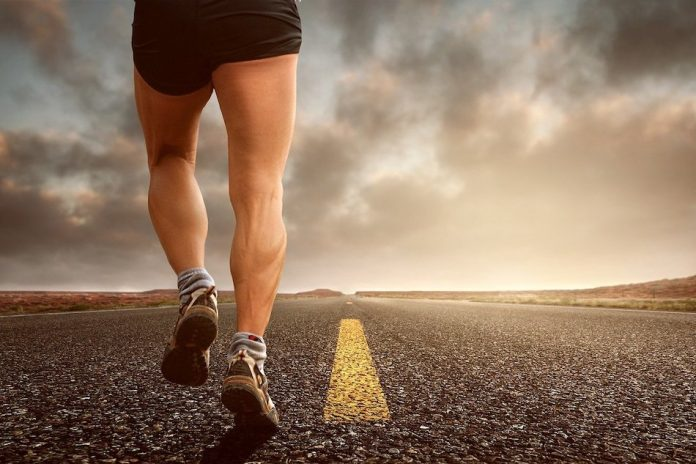 back of mans legs on road jogging