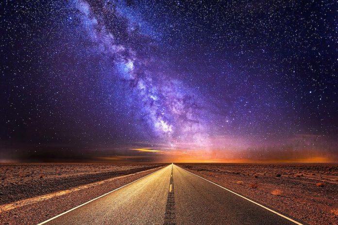 milky way above a road heading into the horizon