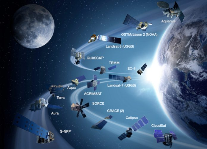 A drawing from 2013 depicting the 17 NASA satellites that were in space at the time, shown orbiting the earth with the moon in the background.