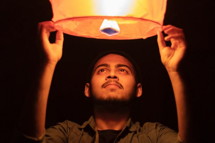 man holding a sky lantern looking into the flame that is inside about to let it go