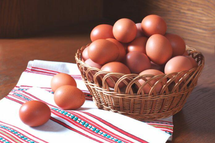 A basket of brown eggs sits on a white towel with red, blue, and green pattern sitting on a wooden surface.