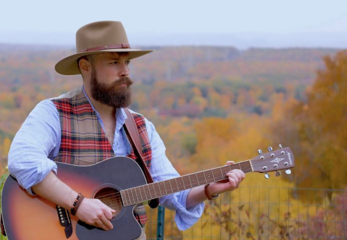 man with beard and hat holds guitar autumn leaves in background