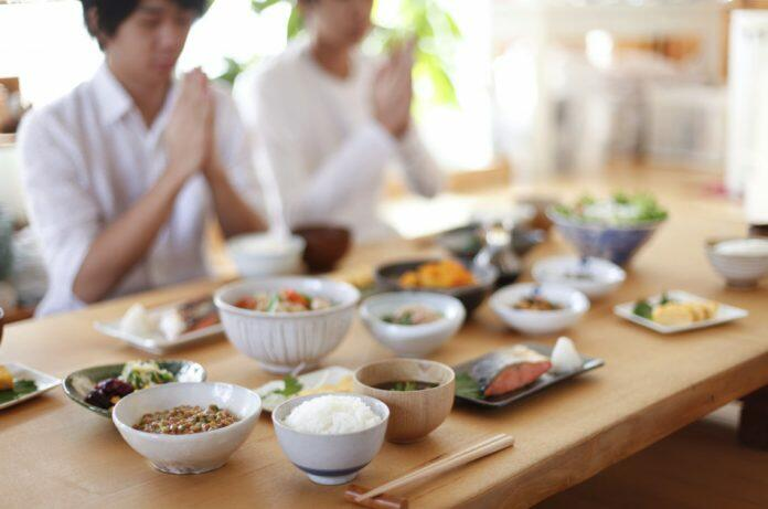 Japanese mealtime: A table loaded with dishes for breakfast and a Japanese family sitting with hands clasped to show gratitude for the meal.