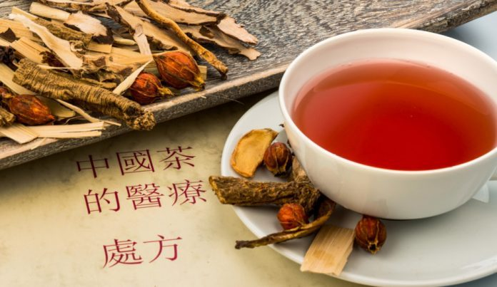 Herbal ingredients sit on a board next to a cup of tea brewed from them.
