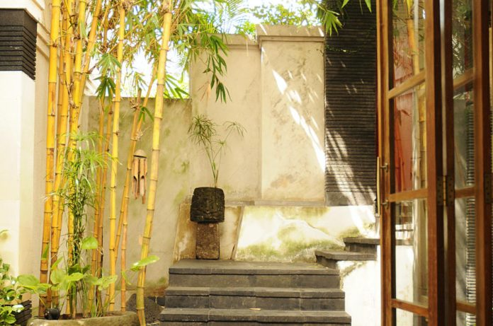 A courtyard with bamboo and wind chimes.