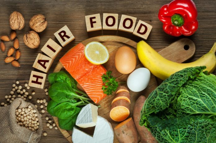 Best foods for healthy hair such as salmon, spinach, almonds, sweet potatoes, eggs, walnuts, cabbage, cheese, red pepper, banana and soy are sitting on a table with blocks spelling out 'hair food'.
