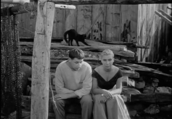 man sits by a lady and black cat strethces in background in Agnes Varda film La Pointe Courte