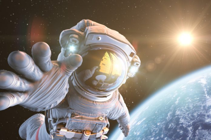 Astronaut on a space walk reaching toward the camera with Earth and the Sun seen in the background.