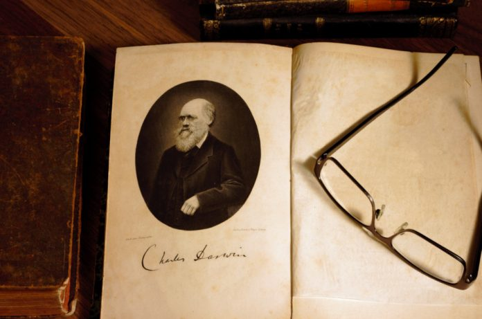 Charles Darwin`s `The origin of species` German translation, 4th edition published in 1870, surrounded by other 19th century books.