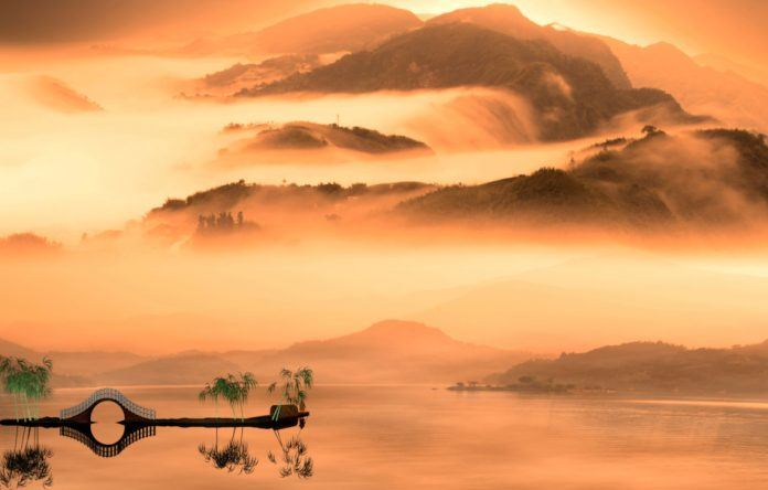 Chinese style painting with water and bridge in foreground and misty mountains in background.