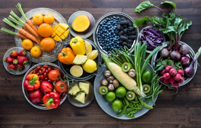 Fruits and veggies grouped by color sit in bowls on a wooden surface.