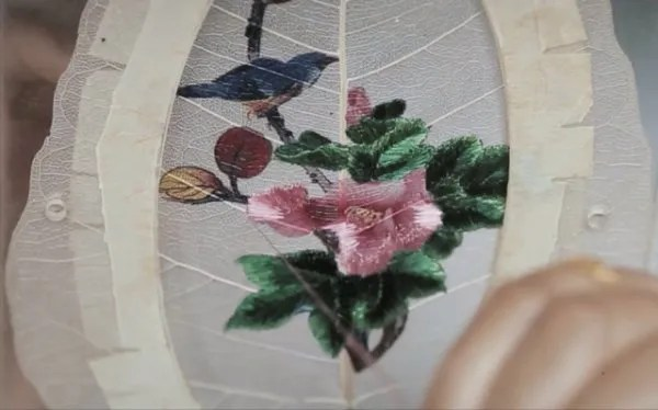 A leaf being embroidered with a blue bird sitting on a branch.