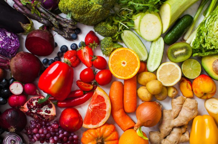 Rainbow colored fruits and vegetables including purple cabbage and eggplant, red peppers and strawberries, orange carrots and citrus fruits, green onions and broccoli, and yellow peppers and squash.