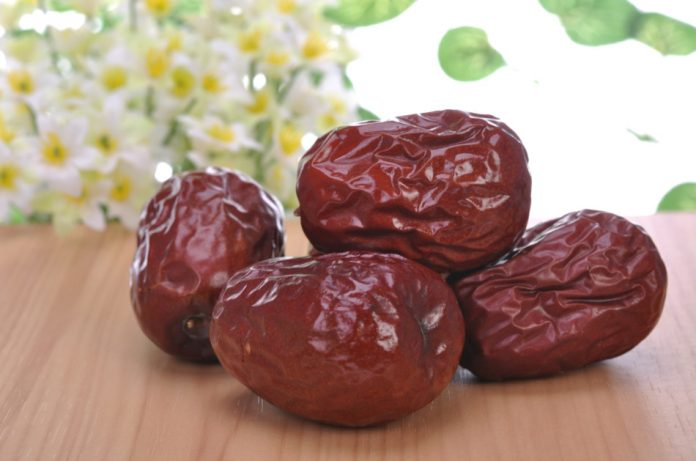 Red dates sitting on a table with flowers and plants in the background.